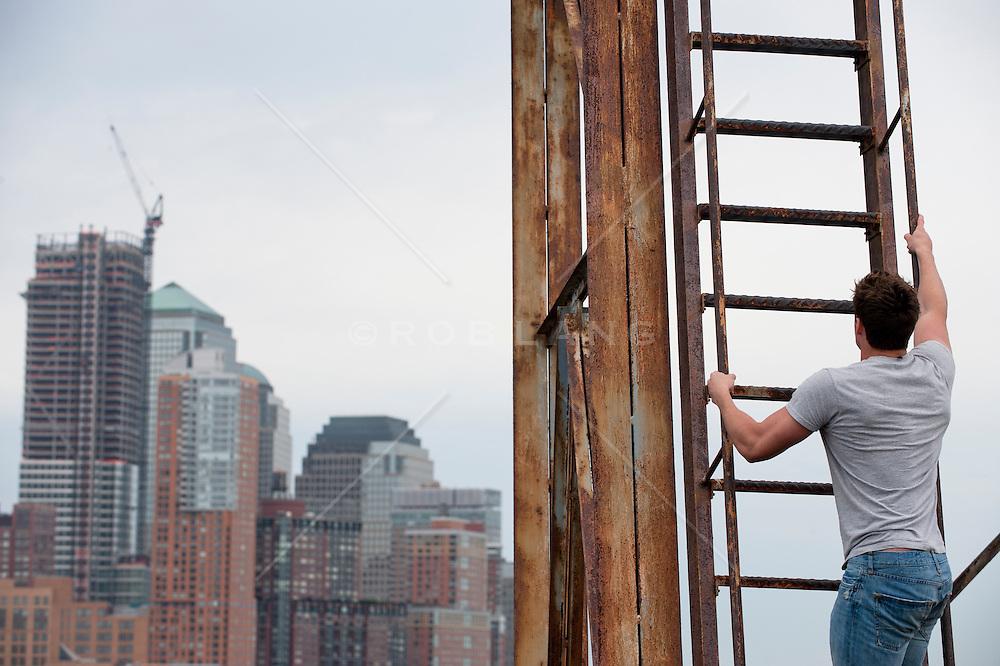 Man climbing up an industrial ladder with a view of Lower Manhattan
