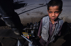 Kabul on the road. .A young Afghan sells fuel for motor vehicle