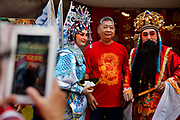 Chinese tourist being photographed with mythalogical chinese characters during the Chinese New Year Celebrations in Thanon Yaowarat, the main thoroughfare which threads through Bangkok's Chinatown, Thailand.