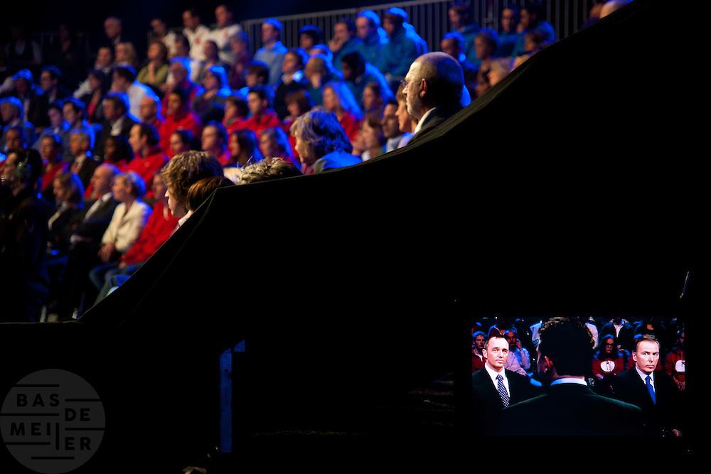 Het publiek kijkt in de studio naar het debat. De avond voor de verkiezingen van de Provinciale Staten wordt in een studio in Baarn nog een debat gevoerd. Het debat wordt door de oppositie gevoerd door de lijsttrekkers van de Tweede Kamer, de gedoogcoalitie vaardigt de lijsttrekkers van de Eerste Kamer af. Via de Provinciale Statenverkiezing wordt indirect ook de Eerste Kamer gekozen.<br /> <br /> The audience is watching the debate in the studio. The evening before the elections for the Dutch districts, who will choose the senators, the political leaders are debating on television.