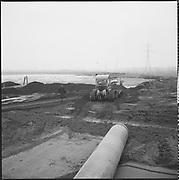 """ackroyd-P011-11. """"... construction on Swan Island April 2, 1964"""" (laying dredge pipe)"""