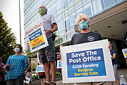 25 AUGUST 2020 - DES MOINES, IOWA: THOMAS DOYLE, (center) and KELLY ALBRECHT (right), retired postal workers from Ft. Dodge, IA, participate in a rally to save the Postal Service at the Neal Smith Federal Building in Des Moines. About 100 people, postal workers and members of the public, came to the Neal Smith Federal Building Tuesday to call for increased spending for the US Postal Service and an end to attacks on the USPS by members of the Trump administration. The rally was a part of a series national rallies organized by the American Postal Workers Union (APWU). Many of the people at the rally expressed concerns that the President's actions versus the USPS could harm their ability vote by mail in the November general election.    PHOTO BY JACK KURTZ