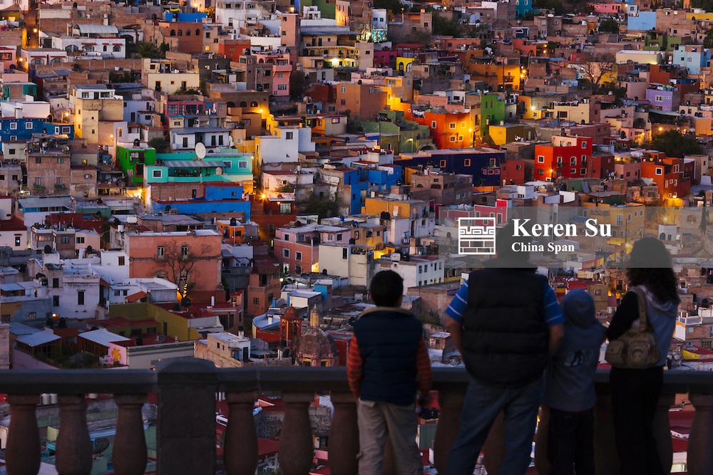 Tourists watching cityscape dominated by Basilica de Nuestra Senora De Guanajuato at sunset, Mexico