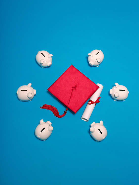 Graduation mortarboard and diploma sitting in the middle of a circle of piggy banks on a blue background