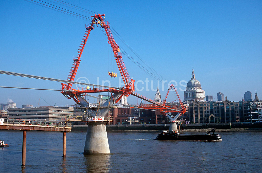 A 1999 landscape showing the construction of the new Millennium Bridge over the river Thames, opposite St. Pauls Cathedral in the City, on 16th February 1999, in London, England. The £18.2m Millennium Bridge a Thames crossing linking the City of London at St. Pauls Cathedral with the Tate Modern Gallery at Bankside was Londons newest river crossing for 100-plus years and coincided with the Millennium, it was hurriedly finished and opened to the public on 10 June 2000 when an estimated 100,000 people crossed it to discover the structure oscillated so much that it was forced to close 2 days later. Over the next 18 months designers added dampeners to stop its wobble but it already symbolised what was embarrassing and failing in British pride. Now the British Standard code of bridge loading has been updated to cover the swaying phenomenon, referred to as Synchronous Lateral Excitation.