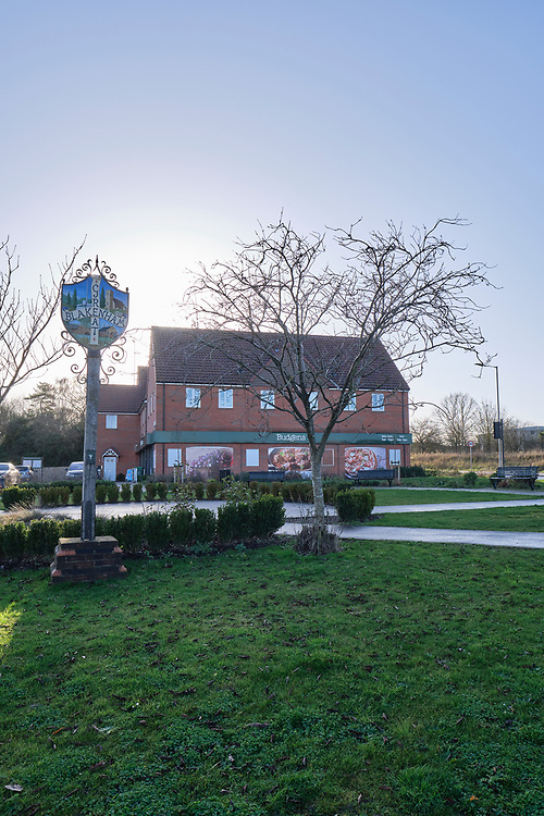 Great Blakenham village sign & green. The Budgens convenience store on the background with flats above.<br /> Photo by Jonathan J Fussell, COPYRIGHT 2020