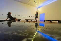 "© Licensed to London News Pictures. 20/07/2018. LONDON, UK. Staff members view ""FLOOR 2015"", a large scale kaleidoscopic work, by Jenny Holzer at the preview of ARTIST ROOMS: Jenny Holzer at Tate Modern. The annual free display includes text-based installations and paintings by the American artist Jenny Holzer and runs 23 July to summer 2019.  Photo credit: Stephen Chung/LNP"