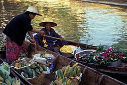 Asia, Thailand, 104 km southwest of Bangkok. Damnoen Saduak Floating Market. Flower and fruit vendors meet on canal