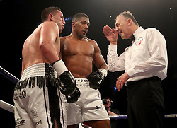 Referee Giuseppe Quartarone speaks with Joseph Parker (left) and Anthony Joshua for use of the head in their WBA, IBF, WBO and IBO Heavyweight Championship contest at the Principality Stadium, Cardiff.