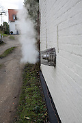 Steam escaping from vent outside house showing loss of energy from domestic heating system
