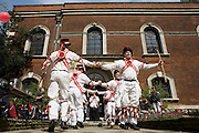 A traditional band of Morris Men dance outside the ancient Christian church of St. Botolph's without Bishopsgate in the City of London on St George's Day. Wearing white uniforms they jig their traditional dance, a form of English folk dance accompanied by accordion and pipes. It is based on rhythmic stepping and the execution of choreographed figures by a group of dancers. Implements such as sticks, swords, and handkerchiefs may also be wielded by the dancers. In a small number of dances for one or two men, steps are performed near and across a pair of clay tobacco pipes laid across each other on the floor. English records of Morris dancing date back to 1448. The church may have survived the Great Fire of London unscathed, and only lost one window in the Second World War, but on 24 April 1993 was one of the many buildings to be damaged by an IRA bomb.