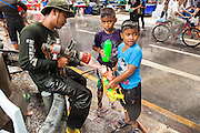 14 APRIL 2013 - BANGKOK, THAILAND:  Boys reload their water guns with help from a Bangkok firefighter on April 14, 2013 in Bangkok, Thailand. The Songkran festival is celebrated in Thailand as the traditional New Year's Day from 13 to 15 April. The throwing of water originated as a way to pay respect to people and is meant as a symbol of washing all of the bad away. PHOTO BY JACK KURTZ