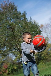 Young boy catching red football happy