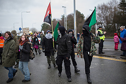 © Licensed to London News Pictures . 26/01/2014 . Salford , UK . Approximately 500 protesters march to an iGas fracking exploration site at Barton Moss , Salford , today (Sunday 26th January 2014) . They walk along the A57 road , blocking traffic as they do . A long term protest camp has been established on an access road leading to the site and today (26th January) protesters from other areas of the country travelled to the site to join with other protesters against fracking . Photo credit : Joel Goodman/LNP