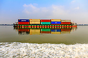 Cargo Container Barge traveling on the Mekong River carrying shipping containers