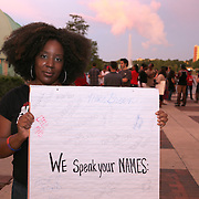 """Shani Angela holds a sign of victims names that were previously brutalized or harassed by the police, during the """"National Moment of Silence"""" event at the Lake Eola bandshell in downtown Orlando, Florida on Thursday, August 14, 2014. In light of the recent killing of eighteen year old Mike Brown in Ferguson, Missouri, citizens across America are gathering in solidarity to hold vigils and observe a moment of silence to honor victims of suspected police brutality. (AP Photo/Alex Menendez)"""