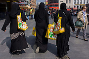 Muslim women in Islamic dress on a shopping trip in London's West End. Having visited the M&M shop in Leicester Square, the three women make their way carrying the spoils of retail therapy, large yellow bags with the cartoon characters' faces. Against the back of their dress, the bright colours are prominent and obvious as to their previous location. In the background are people in clothing suggesting a western culture.