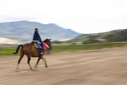 South America, Ecuador.  Man riding horse on dirt road with moutain in distance (blurred motion).