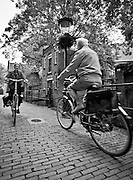 Two senior citizens passing on bikes in Gouda, Netherlands
