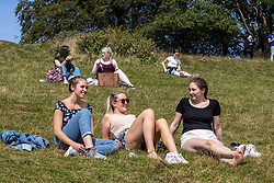 Licensed to London News Pictures. 24/08/202. Dorking, UK. Uni friends Gabriella Smith 26, Jessica Walker 26 and Jessie Lenten 25 enjoy sunbathing in the warm sunshine with highs of 23c on Box Hill in Surrey today. Weather forecaster predict the mild weather will continue this week with a sunny outlook for the Bank Holiday weekend with highs of 21c. Photo credit: Alex Lentati/LNP