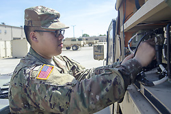 May 16, 2017 - Fort Campbell, Kentucky, U.S. -  By taking leave in May instead of April so he could see his little sister graduate from high school, Army Spc. Jesse Thepouhthay missed out on one of his favorite holidays -- New Year. Most Americans generally associate New Year's celebrations with Dec. 31 and Jan. 1. However, Thepouhthay and his family celebrate Laotian New Year in April. The tradition is carried on by his family in his home town in Arkansas. Food is an important part of the celebration, and missing out on spicy papaya salad this year was a bit of a disappointment, Thepouhthay said. Pictured: Army Spc. Jesse Thepouhthay, an air traffic control equipment repairer assigned to Foxtrot Company, 6th Battalion, 101st General Support Aviation Battalion, at Fort Campbell, Ky., checks a vehicle in the motor pool, May 16, 2017. Thepouhthay's role model is his father, who immigrated to America from Laos. (Credit Image: ? Leejay Lockhart/Army/DOD via ZUMA Wire/ZUMAPRESS.com)