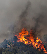 A cross is burning on the top the hill during a wildfire, Friday May 31, 2013, near Castiac, California. Fourteen aircraft and more than 550 firefighter were deployed in a ground and air campaign against a brush fire that has blackened about 1,500 acres in sparsely populated San Francisquito Canyon in the Angeles National Forest northeast of Santa Clarita. The Powerhouse Fire, which broke out Thursday afternoon, was about 15 percent contained. The estimated date of full containment is Wednesday, June 5. (Photo by Ringo Chiu/PHOTOFORMULA.com)