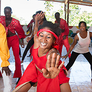 CAPTION: Members of Troupe Dahomey practice a dance routine. At times, when the troupe is rehearsing, young people also join them in order to learn how to play the music or do the dances. ORGANIZATION: Troupe Dahomey / Sant Pont Ayiti (SPA). LOCATION: La Fleur du Chaine, Rue Capois, Port-au-Prince, Haiti. INDIVIDUAL(S) PHOTOGRAPHED: From left to right (full faces visible): Marc-Elise Pierr, David Dunosier, Louis Oldin and Morelus Elizabeth.