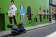 Large scale action figures wearing fashionable clothing against a huge green hoarding which covers the Balenciaga store during a refit in the upmarket area of Knightsbridge on 14th April 2021 in London, United Kingdom. Knightsbridge is one of the principal areas for exclusive, luxury goods in West London. It is known as a district where the rich and wealthy shop, mostly for high end fashion and jewellery. Balenciaga is a luxury fashion house founded in 1917 by Spanish designer Cristóbal Balenciaga.