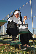"""Humorous photograph of a nun in a habit smoking a cigar at a baseball field and holding a Die Hard battery visually depicting the saying """"Bad habits die hard!"""""""