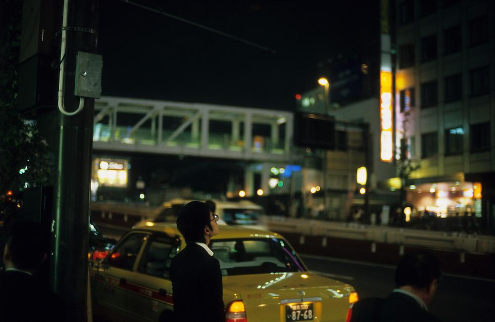 South of Shinjuku station, Tokyo, Japan. A young businessman waits to cross the road at night.