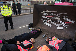 London, UK. 8 December, 2019. Climate activists from Extinction Rebellion, including one (c) on the 21st day of a hunger strike, stage a lie-in in front of a full-scale mock-up of a bulldozer outside Heathrow airport during a Bikes Against Bulldozers protest against Heathrow expansion and the greenwashing of climate commitments by political parties. The protest took the form of a Critical Mass bicycle ride from Hyde Park followed by the lie-in to which Boris Johnson and John McDonnell were invited in order to fulfil their pledge of lying down in front of bulldozers to be used for Heathrow expansion.