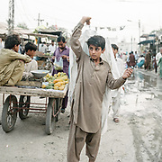 A boy carries a white shirt out of the dry cleaner. The traditional Pakistani Shalwar Kamiz is a large breathable outfit made to breath to bare the heat.