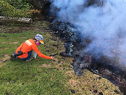 May 6, 2018 - Hawaii, U.S. - As part of their monitoring work, HVO geologists collect samples of spatter for laboratory analysis; information gained from these samples sheds light on what's happening inside Kilauea Volcano. This photo, taken at 10:35 a.m. today, shows fissure 10 near the intersection of Malama and Pomaikai Streets in Leilani Estates (Credit Image: ? USGS/ZUMA Wire/ZUMAPRESS.com)