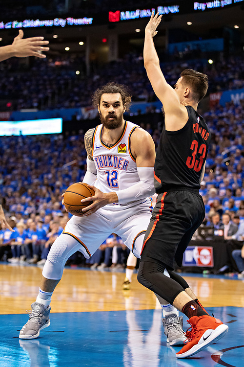 OKLAHOMA CITY, OK - APRIL 21: Steven Adams #12 of the Oklahoma City Thunder looks to get a shot off under the basket against Zach Collins #33 of the Portland Trail Blazers during Round One Game Three of the 2019 NBA Playoffs on April 21, 2019 at Chesapeake Energy Arena in Oklahoma City, Oklahoma  NOTE TO USER: User expressly acknowledges and agrees that, by downloading and or using this photograph, User is consenting to the terms and conditions of the Getty Images License Agreement.  The Trail Blazers defeated the Thunder 111-98.  (Photo by Wesley Hitt/Getty Images) *** Local Caption *** Steven Adams; Zach Collins