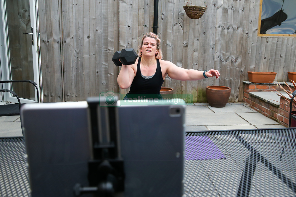 A keen gym worker continues to workout at home with the aid of an online class using an Apple iPad tablet running the Zoom app due to all gyms being closed to the public during the Coronavirus pandemic.