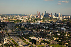 Western aerial view of downtown Houston, Texas skyline with freeway in foreground.