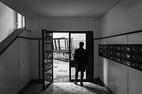 SALERNO (SA) - 3 FEBBRAIO 2018: Un uomo si ripara dalla pioggia all'ingresso alla sede del Partito Democratico di Salerno, città amministrata per 18 anni (dal 1993 al 2011) dall'attuale governatore della Regione Campania Vincenzo De Luca (Partito Democratico), il 3 febbraio 2018.<br /> <br /> Le elezioni politiche italiane del 2018 per il rinnovo dei due rami del Parlamento – il Senato della Repubblica e la Camera dei deputati – si terranno domenica 4 marzo 2018. Si voterà per l'elezione dei 630 deputati e dei 315 senatori elettivi della XVIII legislatura. Il voto sarà regolamentato dalla legge elettorale italiana del 2017, soprannominata Rosatellum bis, che troverà la sua prima applicazione<br /> <br /> ###<br /> <br /> SALERNO, ITALY - 3 FEBRUARY 2018: A man shelters from the rain at the entrance of the headquarters of the Democratic Party (PD / Partito Democratico) of Salerno, a city governed for 18 years by Vincenzo De Luca (Democratic Party / Partito Democratico), currently President of the Campania region, in Salerno, Italy, on February 3rd 2018.<br /> <br /> The 2018 Italian general election is due to be held on 4 March 2018 after the Italian Parliament was dissolved by President Sergio Mattarella on 28 December 2017.<br /> Voters will elect the 630 members of the Chamber of Deputies and the 315 elective members of the Senate of the Republic for the 18th legislature of the Republic of Italy, since 1948.