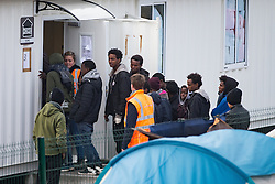 © Licensed to London News Pictures . 24/10/2016 . Calais , France . Unaccompanied children and teenagers queue to leave the Jungle migrant camp in Calais , Northern France , on the day of a planned eviction and start of the destruction of the camp . Photo credit: Joel Goodman/LNP