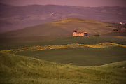 A building sits in the valley of rolling farmland in Tuscany, Italy