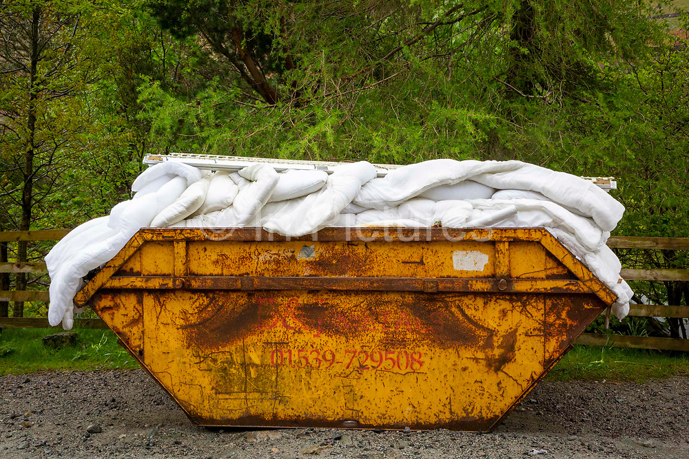 A yellow skip full of old bedding duvets and pillows outside the Youth Hostel Association  Helvellyn, The Lake District, United Kingdom.