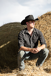 cowboy squatting down next to hay bales