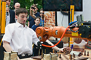 Moscow, Russia, 19/05/2012..Russian grandmaster and former World Blitz Chess Champion Alexander Grischuk reacts to an attacking move by his opponent, the German-built KUKA Monster chess robot. The match was a warm up before the main contest between KUKA Monster and Russia?s CHESSka robot for the title of Absolute World Robot Chess Champion. KUKA Monster easily beat the human Russian grandmaster, but was in turn comprehensively defeated by the Russian robot.