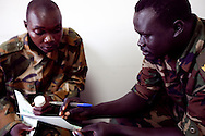 Captain Simon Mojan speaks with Simon Akele an HIV positive soilder about his ART at the BILFAM clinic in Juba where ARVs are distributed.