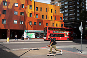 Colourful residential housing block and a passing skateboarder in Elephant and Castle in London, UK. The area is now subject to a master-planned redevelopment budgeted at £1.5 billion. A Development Framework was approved by Southwark Council in 2004. It covers 170 acres and envisages restoring the Elephant to the role of major urban hub for inner South London.