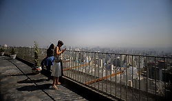 August 28, 2017 - Sao Paulo, Brazil - Tourists enjoy the view at the top of the Copan building, The building was designed by Oscar Niemeyer s office in Sao Paulo; Niemeyer was personally responsible for the building s famous sinuous façade. The idea was a building open to a mixed cross section of Brazilian society. The original project envisioned two buildings, the other being a hotel, but in the end only the residential building was built. (Credit Image: © Dario Oliveira via ZUMA Wire)