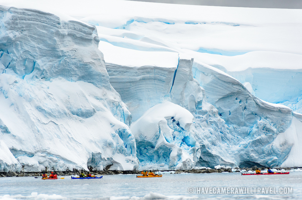Kayakers paddle past massive cliffs of glacial ice slowly sliding into the sea along the waterfront at Melchior Island on the western coast of the Antarctic Peninsula.