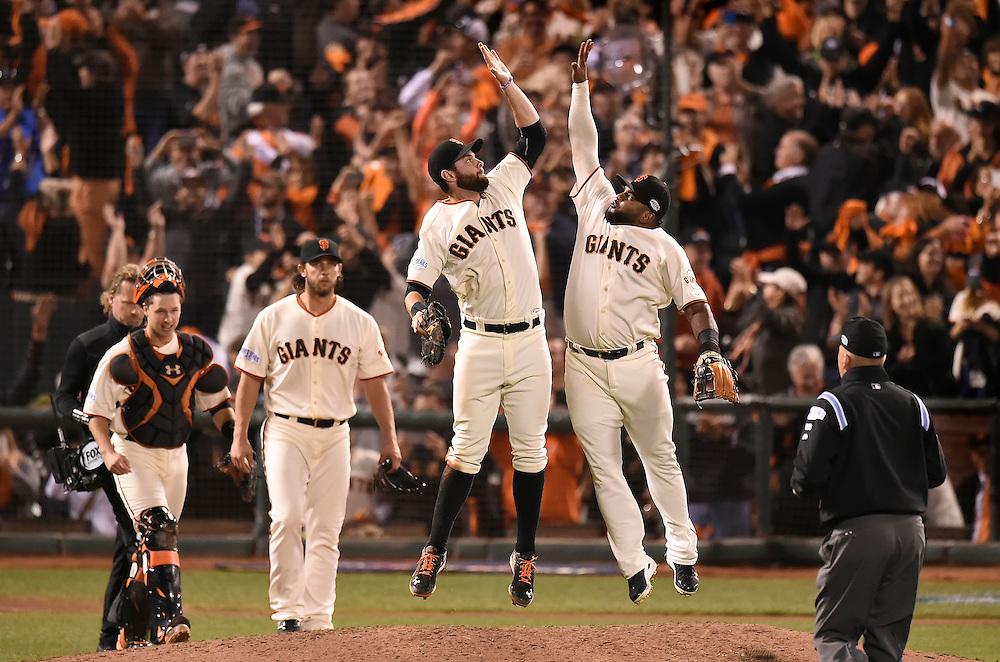 San Francisco Giants first baseman Brandon Belt (center) leaped in the air with third baseman Pablo Sandoval (right) and teammates Buster Posey (left) and pitcher Madison Bumgarner (second from left) after the 5-0 victory over the Kansas City Royals during Sunday's Game 5 of the World Series on October 26, 2014 at AT&T Park in San Francisco, Calif.