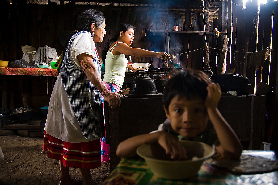 Women cook over a wood burning stove inside their home in the Lacandon Maya community of Naha, Chiapas, Mexico on July 4, 2008 while young Chan K'in Omar eats from his bowl. Ko Maria, left, is one of the four surviving widows of Chan K'in Viejo, the late spiritual leader of the Lacandon, who died in 1994.