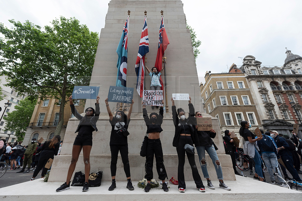 © Licensed to London News Pictures. 03/06/2020. London, UK. Protesters stand on the Cenotaph in Whitehall taking part in a demonstration organised by group Black Lives Matter in Hyde Park for the American George Floyd who died whilst being arrested by US policemen Derek Chauvin. His death has caused civil unrest in some US cities. Photo credit: Ray Tang/LNP
