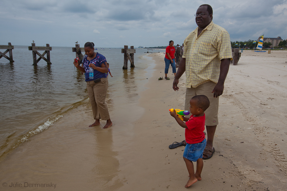 Family on the beach in Biloxi Mississippi  where Oil from the BP oil spill in the Gulf of Mexico reached the beaches .